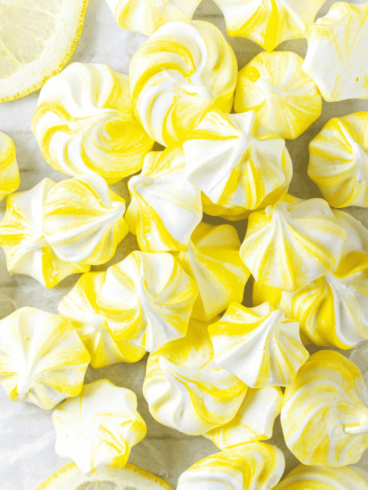 A bunch of lemon meringue cookies on top of one another on a piece of parchment paper.