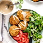 A plate with five falafel balls, lettuce, and tomato slices. A cup of dressing is on the white counter behind the plate.