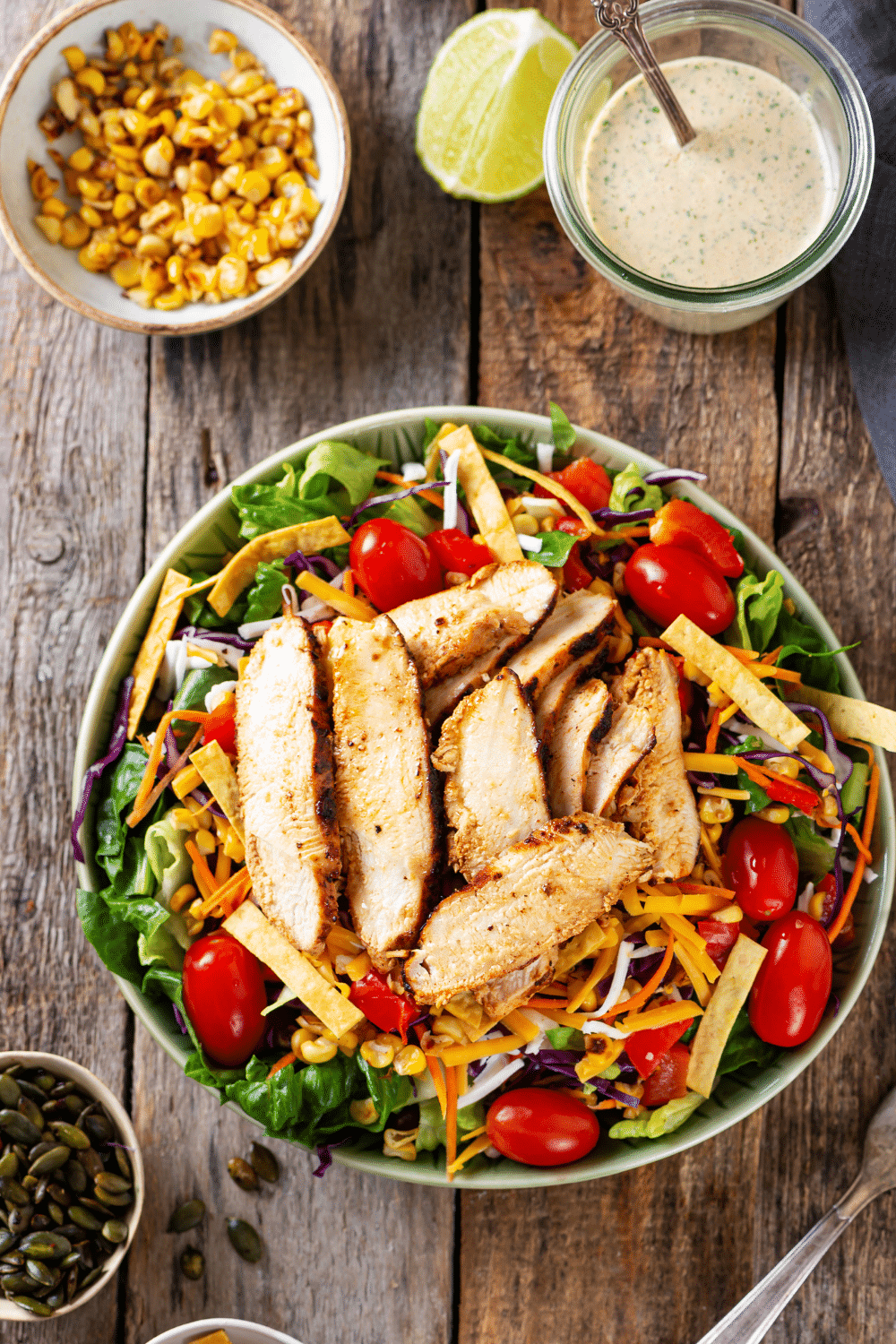 A southwest chicken salad in a white bowl. There is a small white bowl of corn and a small glass jar of creamy salsa behind the bowl..