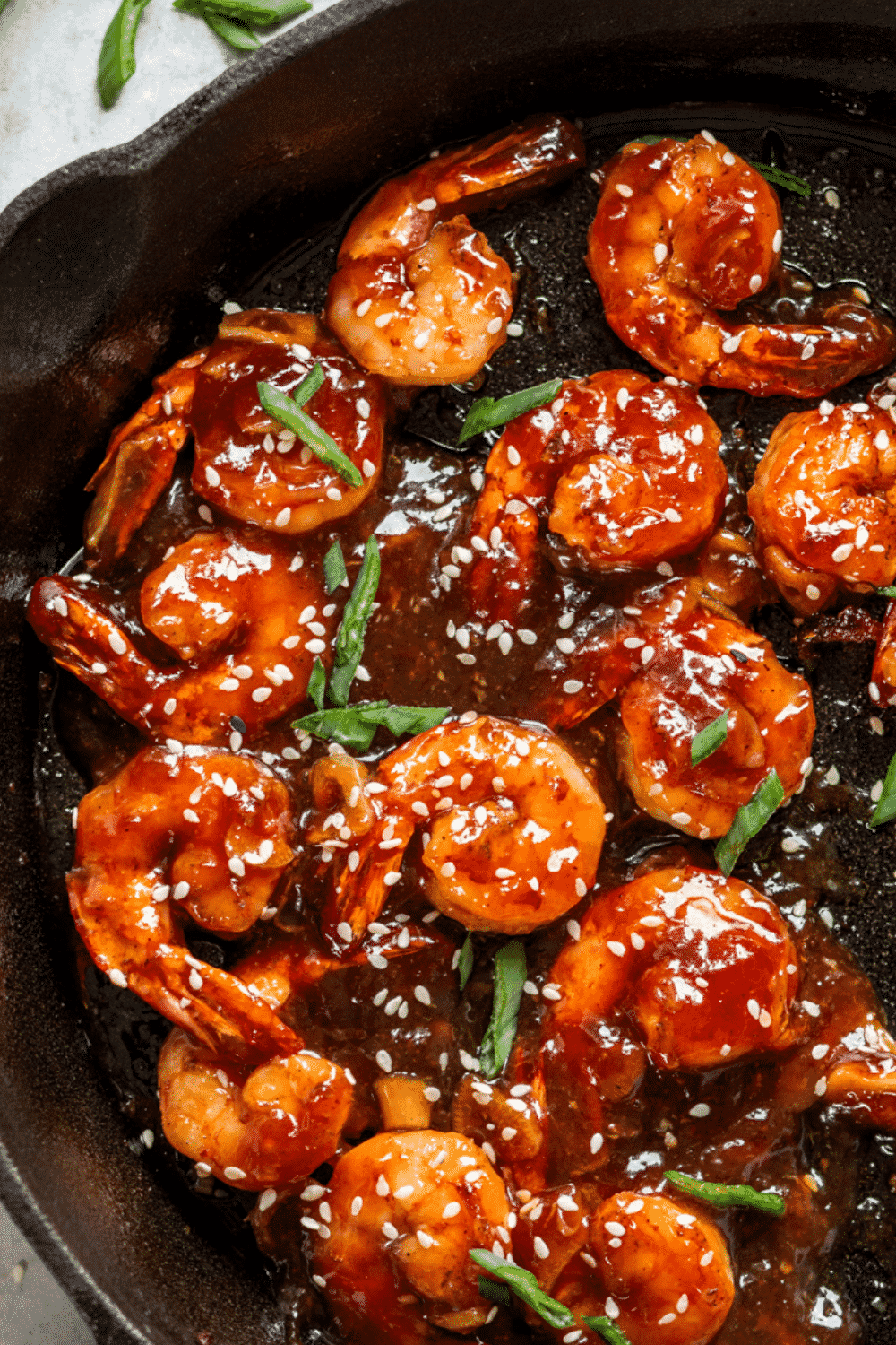 A bunch of sweet and sour shrimp in a skillet.