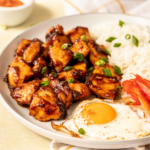 Chicken tocino, a fried egg, part of sliced red bell peppers, and some white rice, on a white plate. The plate is on a white and gold checkered tablecloth on a white counter.