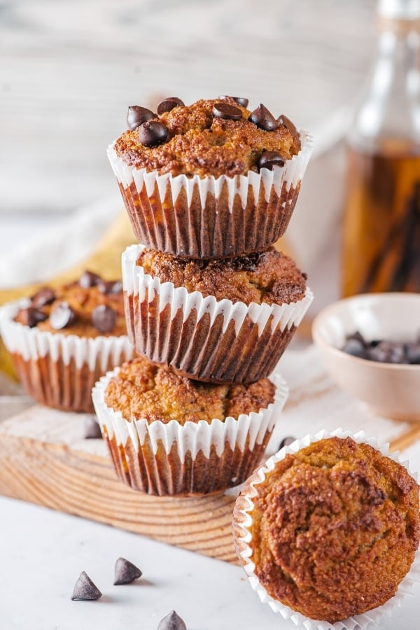 A stack of three almond flour banana muffins on a wooden cutting board. One almond flour muffin is in front of the cutting board with the top showing and a chocolate chip banana muffin is behind the stack on the cutting board.