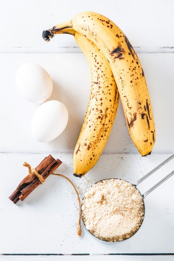 Two ripe bananas, two eggs, cinnamon sticks, and a cup of almond flour and a white counter.