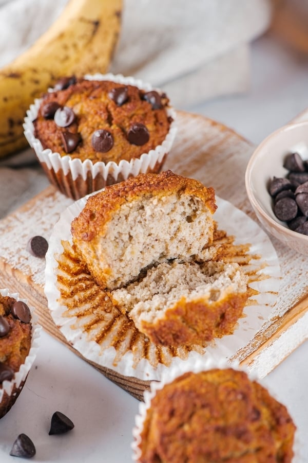 Almond flour banana muffin and a muffin wrapper on a wooden cutting board. The muffin is broken in half with the front half on the bottom of the wrapper in the middle showing. There is a chocolate chip almond flour banana muffin behind it on the wooden cutting board.