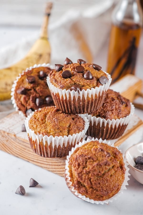 A pyramid of three almond flour muffins on a wooden cutting board. One almond flour muffin with a front facing office in front of the cutting board and a chocolate chip almond flour muffin with the front facing is behind the pyramid..