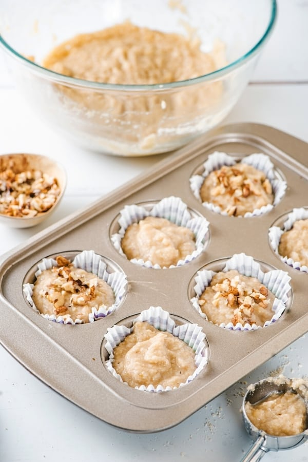 A muffin pan with six slots filled with banana muffin batter. The glass bowl of batter is behind the pan and there is a small bowl nuts in front of it.