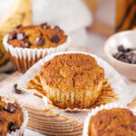 An almond flour banana muffin on top of a muffin wrapper on a wooden cutting board. There is a chocolate chip banana muffin behind it and parts of two banana muffins in front of the cutting board.