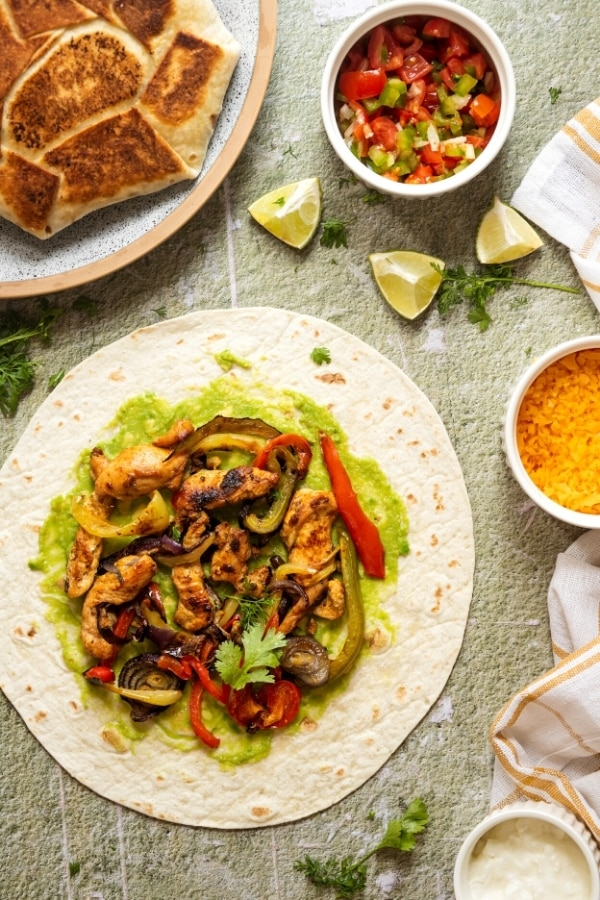 An open flour tortilla with avocado and chicken fajitas on it. Behind the tortilla is part of a plate with a crunch wrap on it and a small bowl of salsa and a small bowl of cheddar cheese next to it.