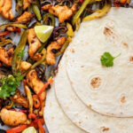 Part of a sheet pan with chicken fajitas on top of parchment paper. There are three flour tortillas overlapping one another on the right of the sheet pan.