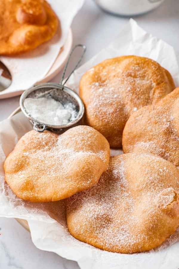 Three whole pieces and part of a piece of dough and a piece of parchment paper in a bowl. There is a small sifter filled with powdered sugar between two pieces of fried dough.