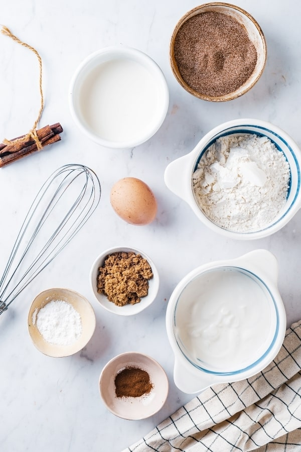 A small bowl of cinnamon sugar, a small bowl of milk next to it, a whisk and egg in front of it, a medium bowl of flour next to the egg, in front of that a medium bowl of yogurt, and to the left a small bowl of cinnamon, a small bowl baking powder, and a small bowl of brown sugar. Everything is sitting on a white counter.