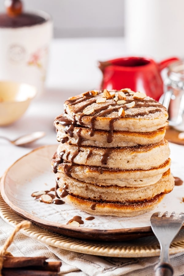 Five churro pancakes with chocolate sauce drizzled on top stacked on a white plate.