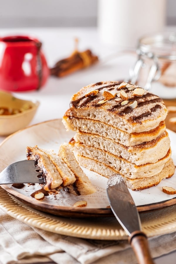White plate with a stack of six churro pancakes on it. The top pancake has some chocolate sauce on top and there is a fork at the front of the plate with three pieces of pancake on the prongs.