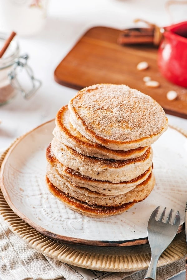 Six churro pancakes stacked on a white plate with the prongs of a fork resting on the front edge of the plate.