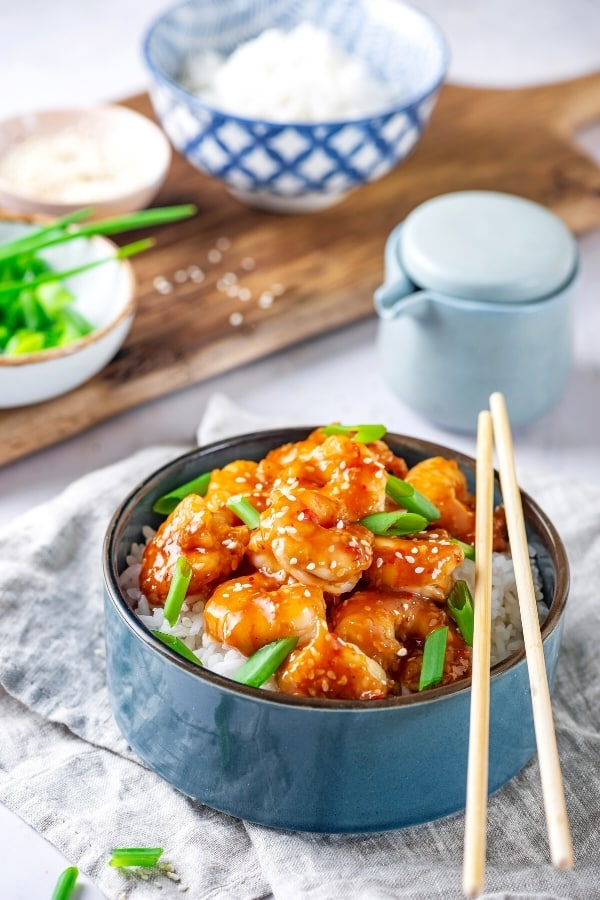 A blue bowl filled with white rice and General tsos shrimp on top with some green onions around the shrimp. Behind the bowl is part of a small bowl of green onions and a bowl filled with white rice on a wooden board.