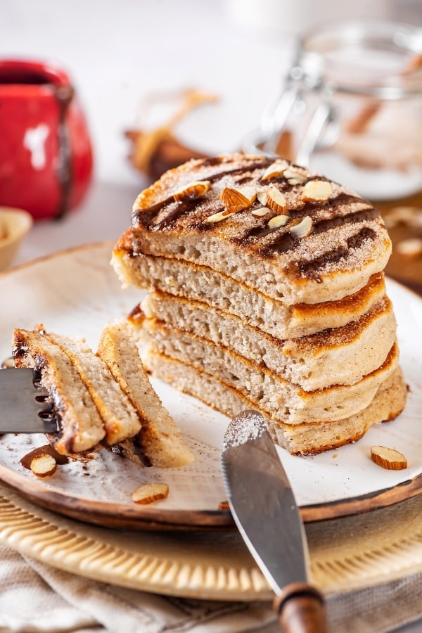 A stack of six churro pancakes on a white plate with a piece cut out of the front of all the pancakes. There are three pieces of pancake on the prongs of a fork at the front edge of the plate.