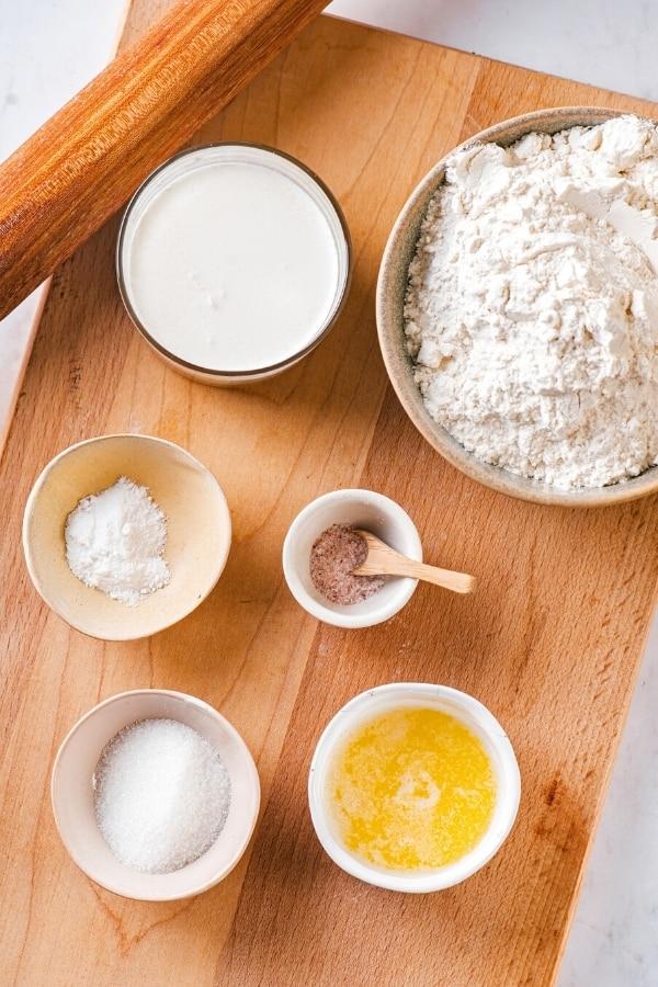 A large bowl of flour, a medium bowl of milk, a small bowl of baking powder, a small bowl of sugar, a small bowl of melted butter, and a small bowl of salt all on a wooden cutting board.