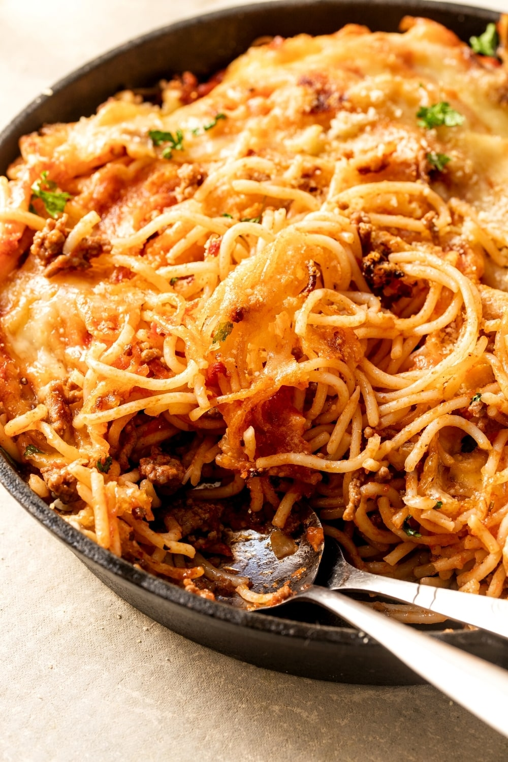A cast iron skillet with fried spaghetti in it. A spoon and fork or at the front of the skillet with some noodles moved from where they are.