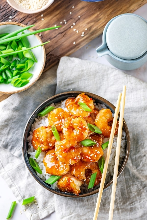 A bowl filled with General tsos shrimp and a few green onions on top of white rice. There are chopsticks at the right side of the bowl and the bowl is on a grey tablecloth. Bhind the bowl on a wooden board is a small white bowl filled with green onions.