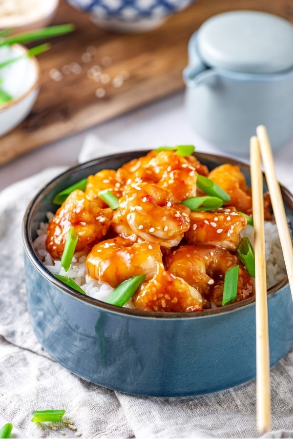 A blue bowl with white rice in it and general Tso's shrimp on top with a few green onions around the shrimp. Part of a pair of chopsticks is on the right of the bowl with the bottoms touching the grey tablecloth underneath the bowl.