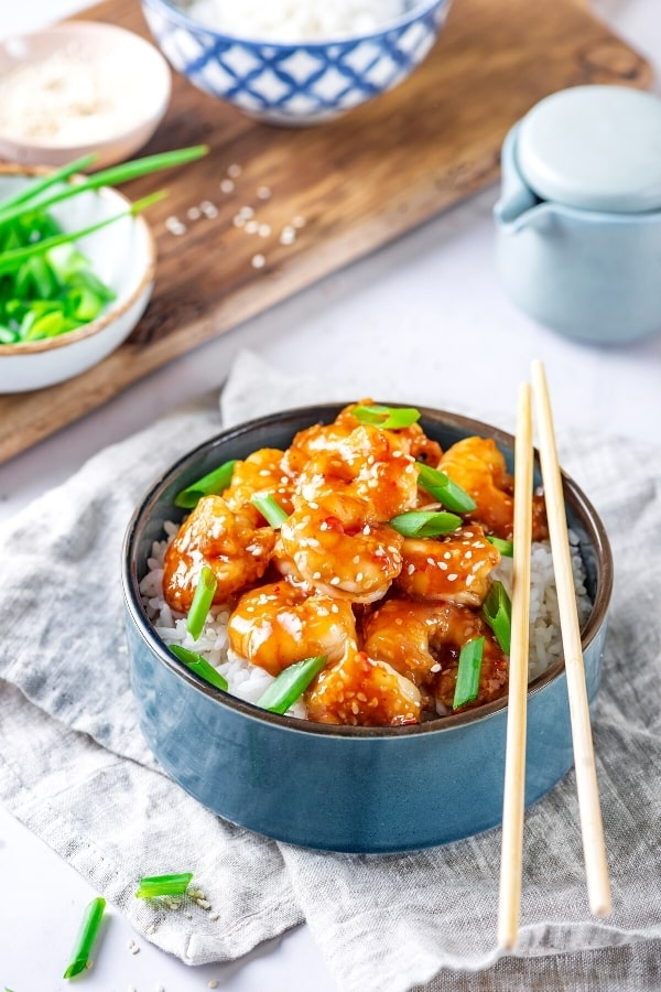 A blue bowl with white rice in it and general tsos shrimp on top with a few green onions. There are chopsticks on the right side of the bowl and the bowl is on a gray tablecloth, in front of a wooden board with part of a bowl of green onions.