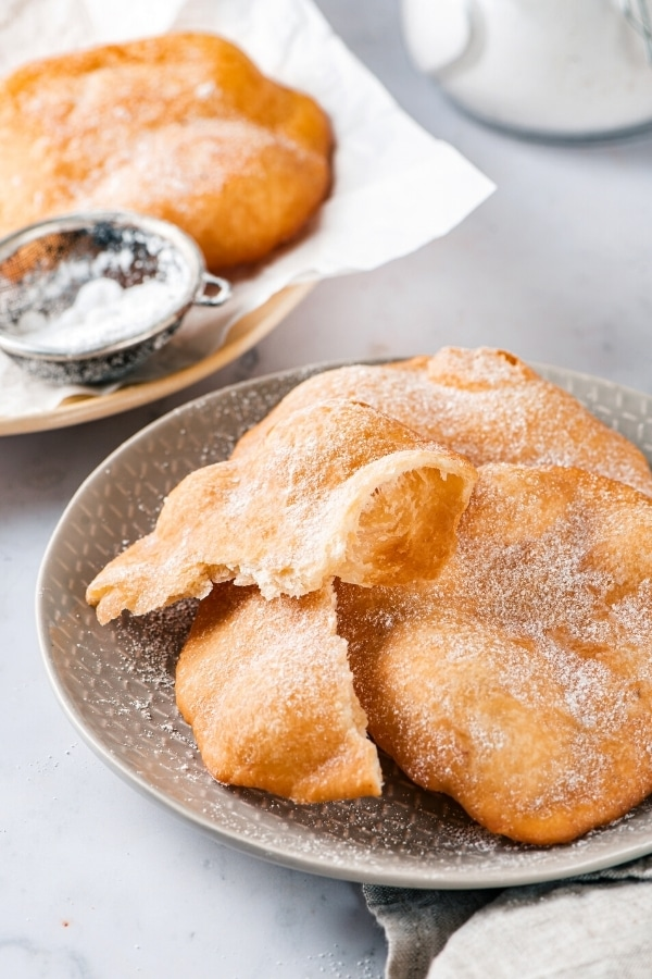 Two pieces of fried dough on top of one another with a broken piece of fried dough all on a gray plate. Behind the plate is another plate with a piece of white parchment paper on it with one piece of fried dough and a small sifter on top.