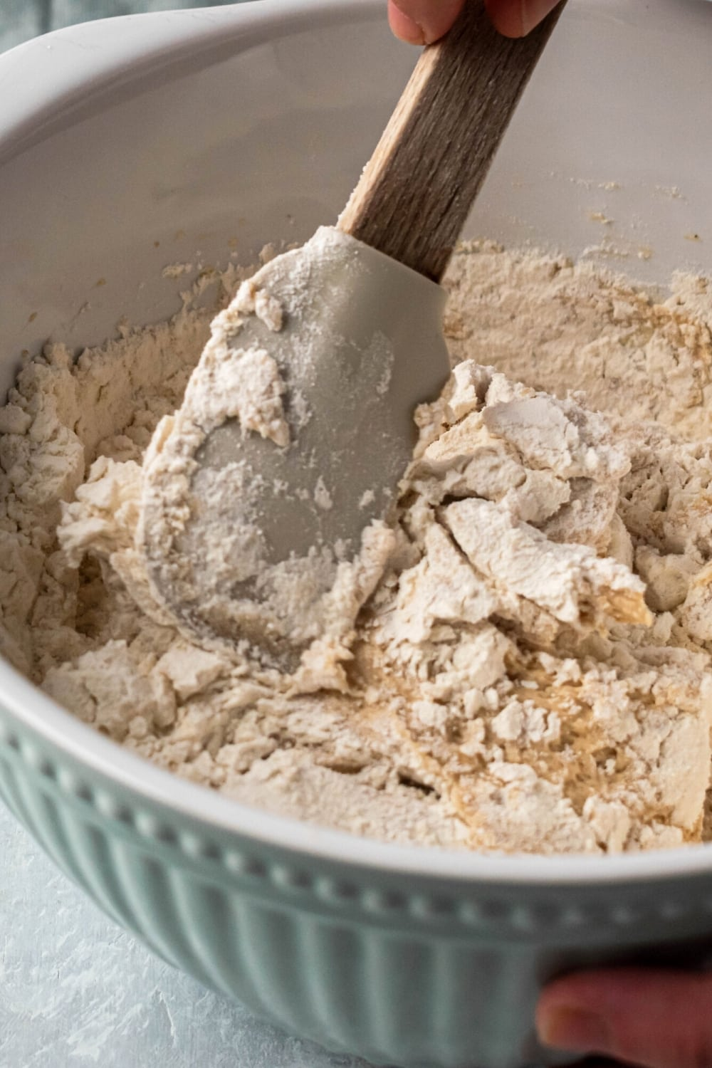 A bowl of cookie dough ingredients with a rubber spatula mixing them together.