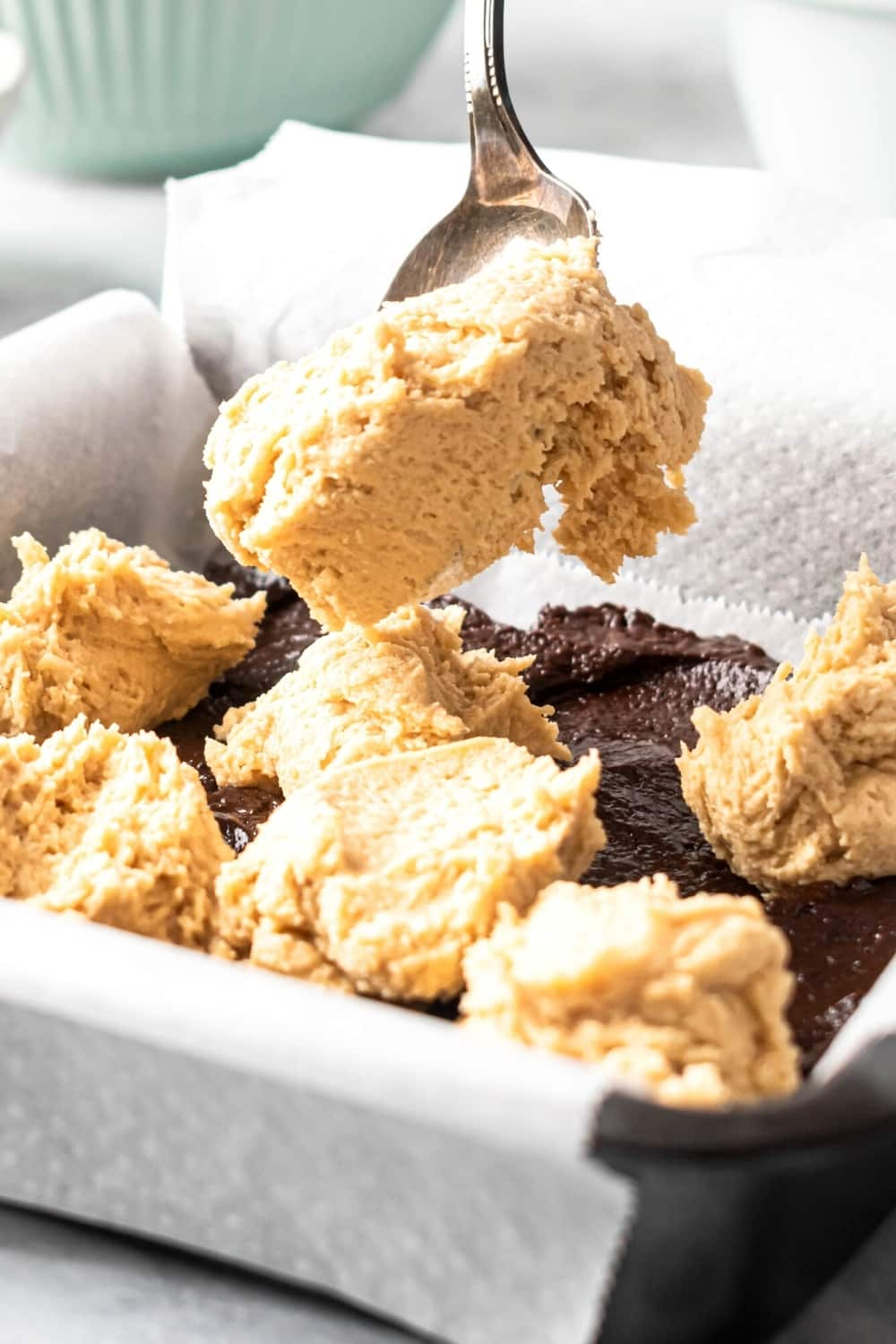 Baking pan lined with parchment paper with brownie batter on it and some balls of cookie dough on top. A spoon is scooping a bowl of cookie dough into the pan.