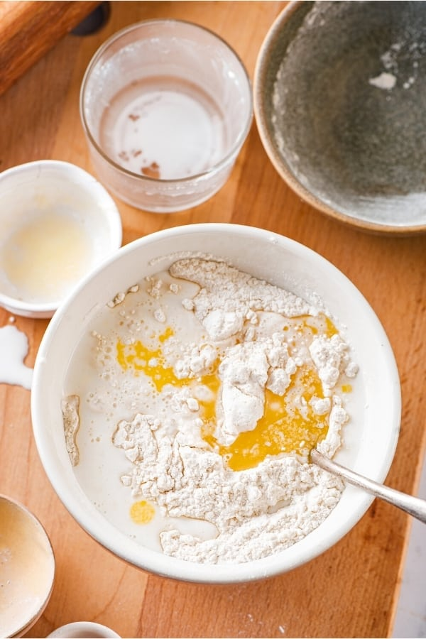 A large white mixing bowl with wet and dry ingredients for fried dough. The empty bowls from the ingredients are behind it and everything is on a wooden cutting board.