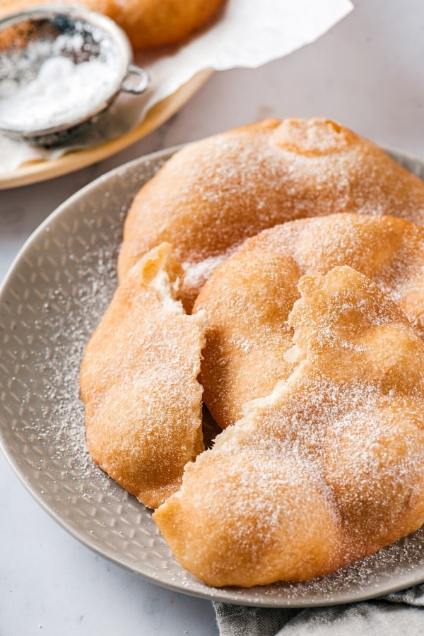 Two pieces of fried dough overlapping one another with a broken in half piece of fried dough at the front of them. All of the fried dough is on a gray plate.