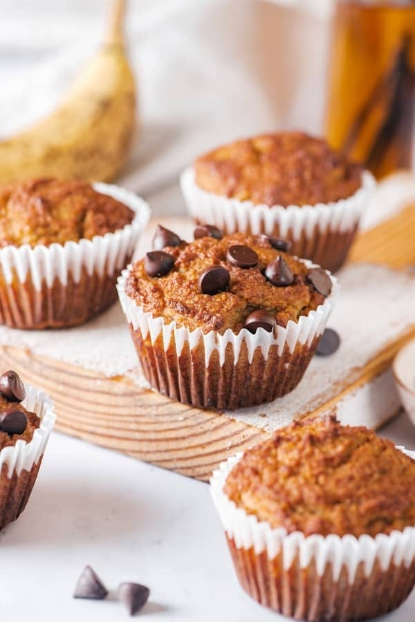 Three almond flour banana muffins on a wooden cutting board. There is one muffin in front of the cutting board with two chocolate chips next to it.