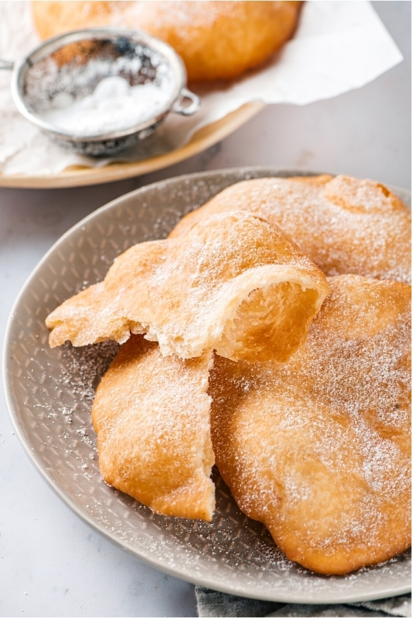 Two pieces of fried dough on top of each other with a broken piece of fried dough next to it all on a gray plate. Behind it is a plate with a piece parchment paper with part of a piece of fried dough and a small sifter.