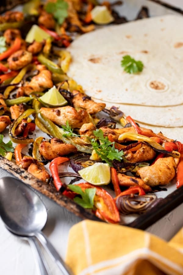 Part of a baking sheet lined with parchment paper with chicken fajitas on top. There is a flour tortilla on top of two other tortillas on the right of the pan.