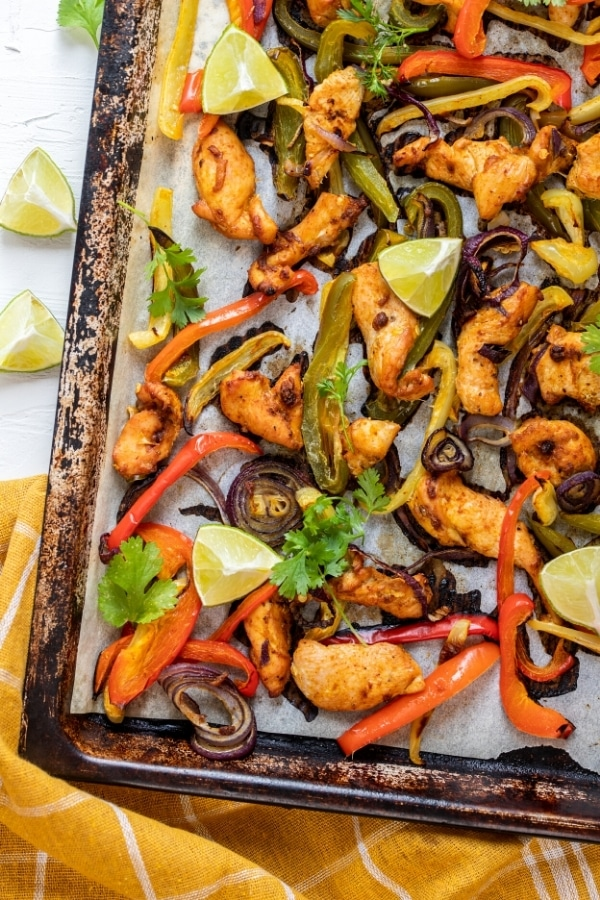 The bottom corner of a sheet pan with parchment paper on it and chicken fajitas on top.