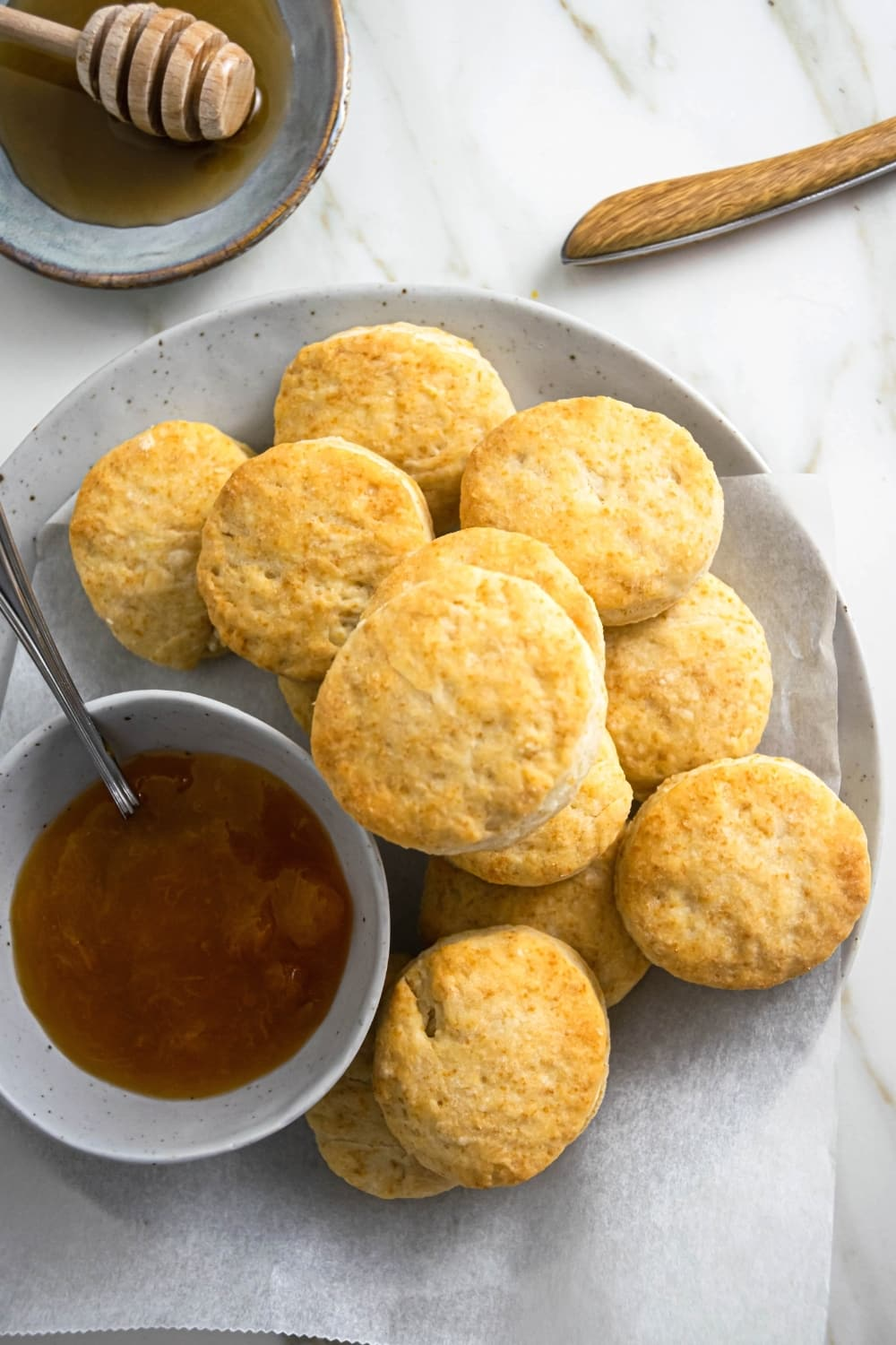 A bunch of biscuits and a piece of parchment paper on a gray plate. Next to the biscuits on the plate is a bowl with gravy with a spoon in it. Behind the plate is part of a bowl of honey. Everything is on a white counter.