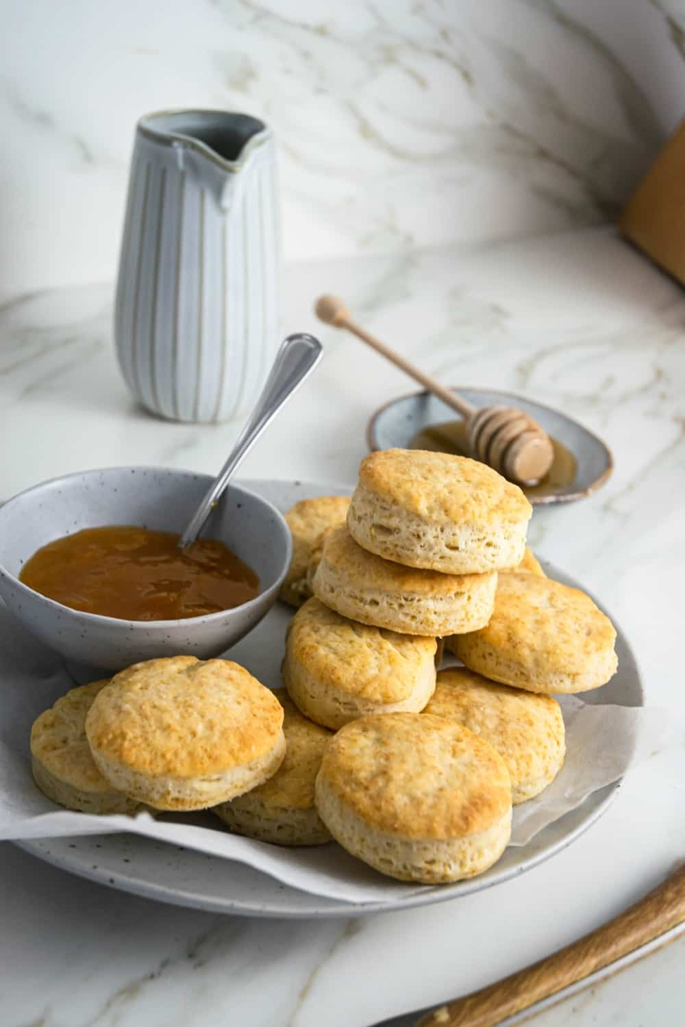 A bunch of biscuits and a piece of parchment paper on a gray plate. There is a bowl of gravy on the plate to the left of the biscuits in behind the plate is a small bowl of honey on a white counter.