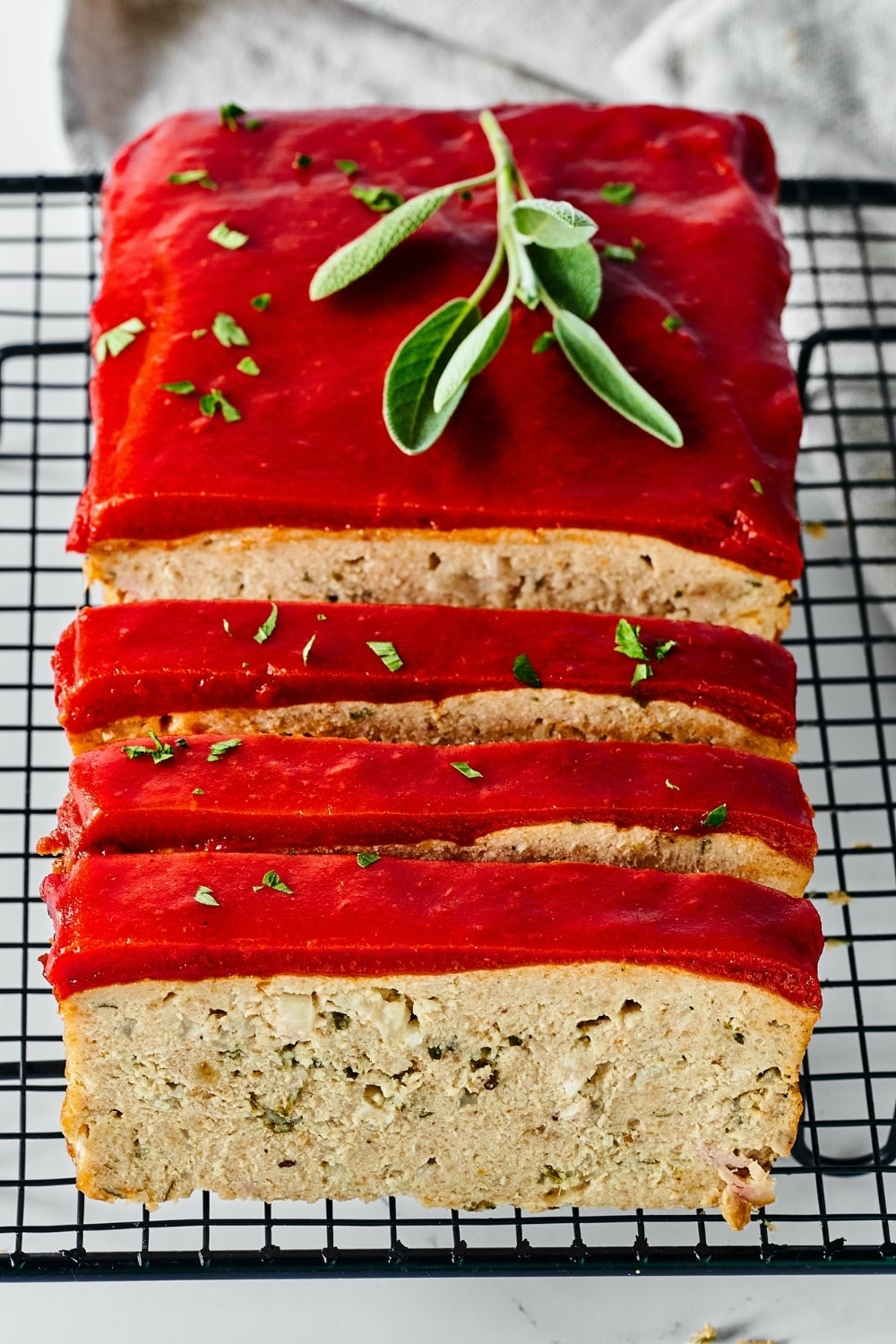 Chicken meatloaf on a black wire rack. There are three slices of meatloaf cut leaning against the rest of the meatloaf.