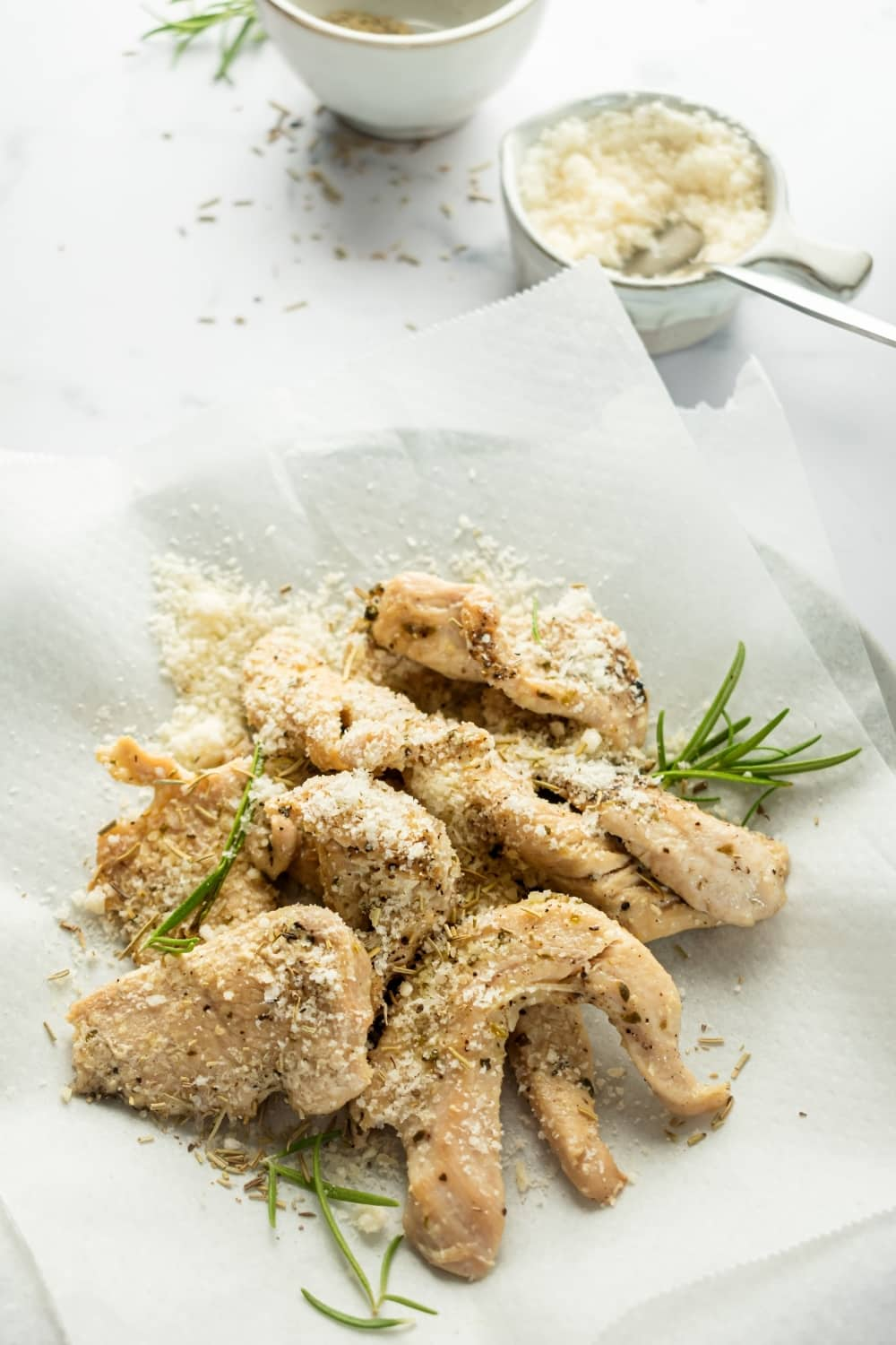 Chicken tenders with some Parmesan cheese on top and a piece of white parchment paper. Behind it is a small bowl of Parmesan cheese with the spoon in the cheese. Everything is on the white counter.