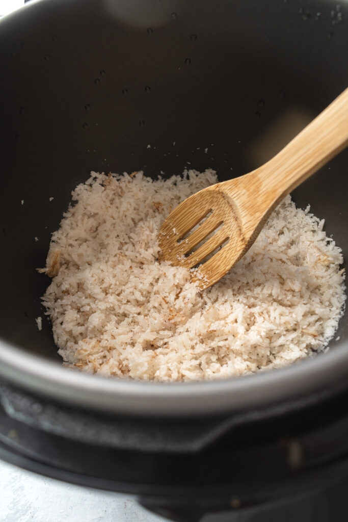 An instant pot with coconut rice in it. There is a wooden spoon in the middle of the rice.