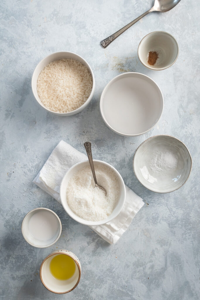 A small bowl of olive oil, a small bowl of coconut milk, a bowl of shredded coconut, a bowl of water, a bowl of rice, and a small bowl of cinnamon on a gray counter.