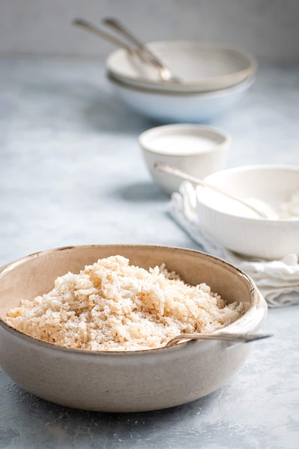 A white bowl filled with coconut rice. There is a fork submerged in the rice and behind the bowl or a few empty white bowls.