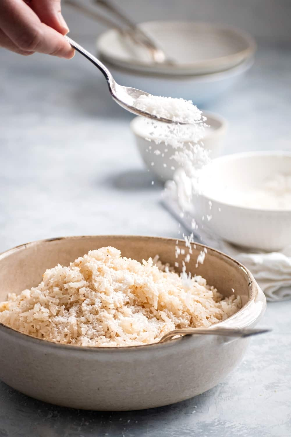 A white bowl with coconut rice in it. A hand is holding a spoon sprinkling shredded coconut on top of the rice.
