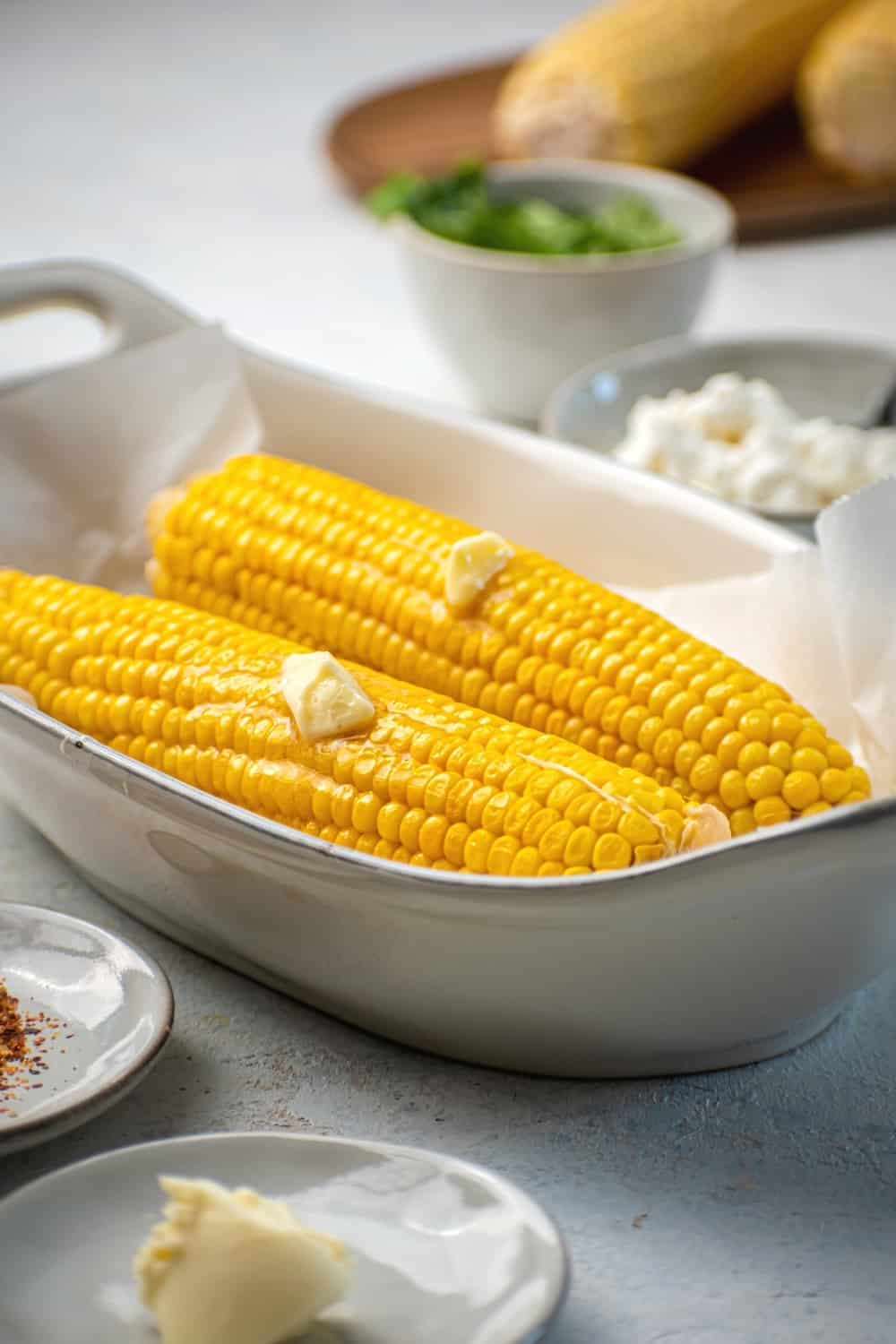 Two pieces of corn on the cob with a slab of butter on them on parchment paper in a white bowl. In front of the bowl is a small plate with butter on it in behind the bowl is a small bowl with mayo in it in and a small bowl of cilantro. Behind that is part of a corn on the cob on a wood board.