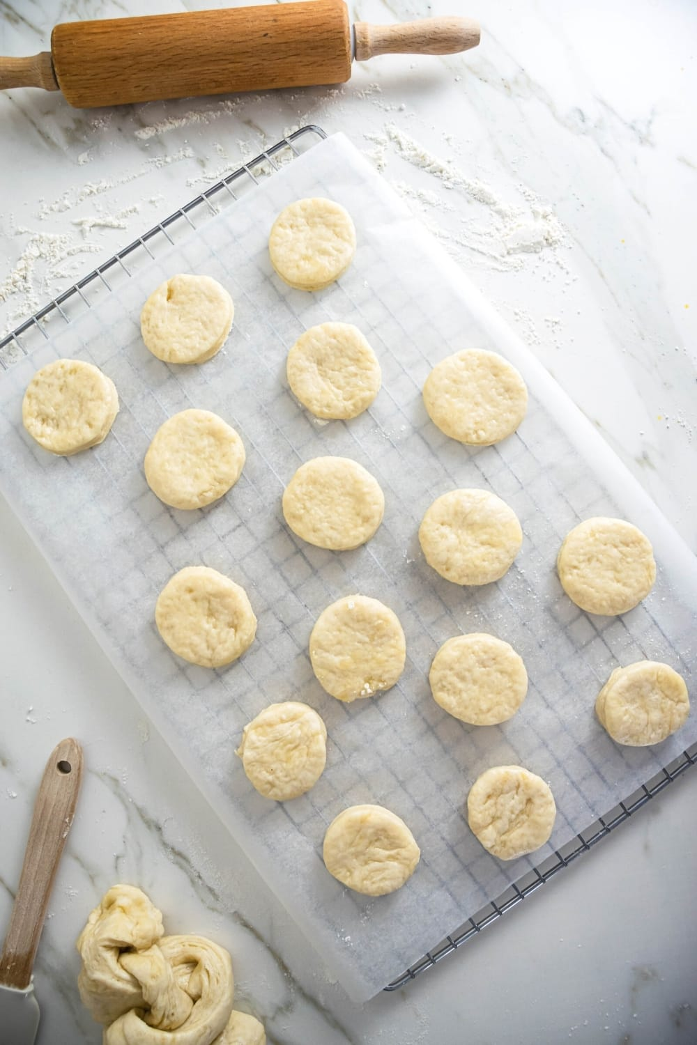 A wire rack with a piece of parchment paper on top and 14 biscuits on it. Behind the wire rack is a rolling pin on a white counter.