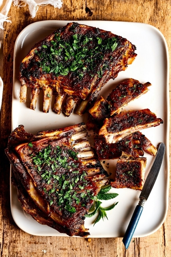 Two lamb breasts and a few slices of lamb breast to the right of them all on a rectangular white plate on a wooden counter.