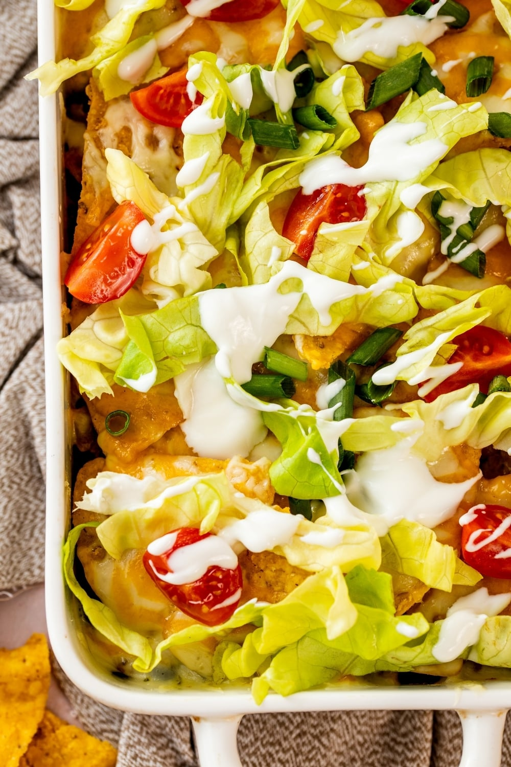 Part of a white casserole dish filled with walking taco casserole. There is lettuce, sour cream, and tomatoes on the top.