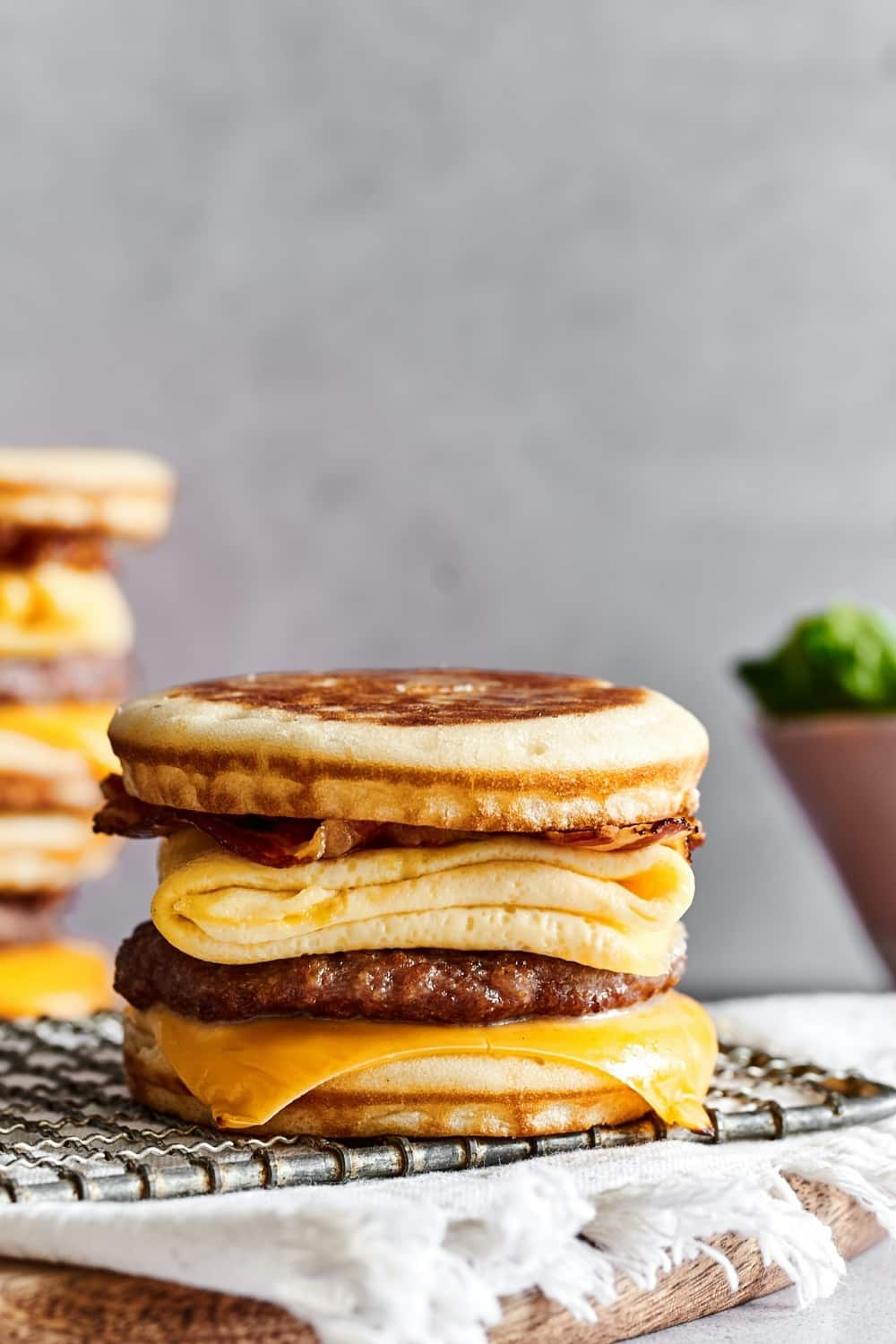 A McGriddle on a wire rack on a White tablecloth cover in a wooden board that is set on a white counter.