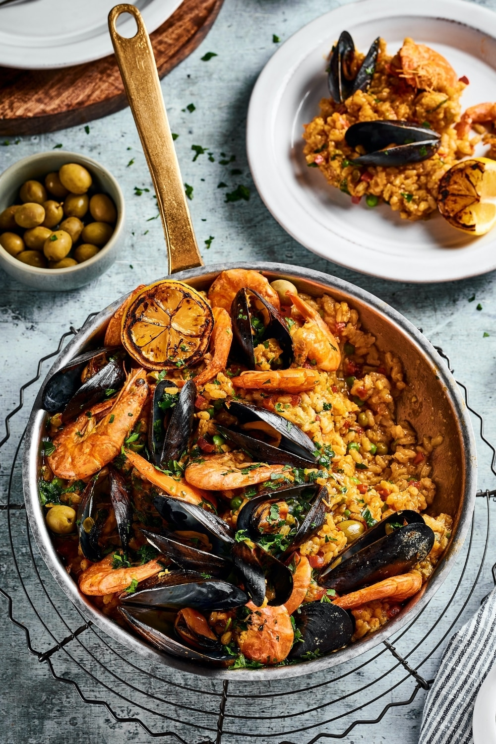 A pan on a wire rack with seafood paella in it. Behind the pan is a white plate with some of the paella on it. To the left of the white plate is a small bowl of olives.