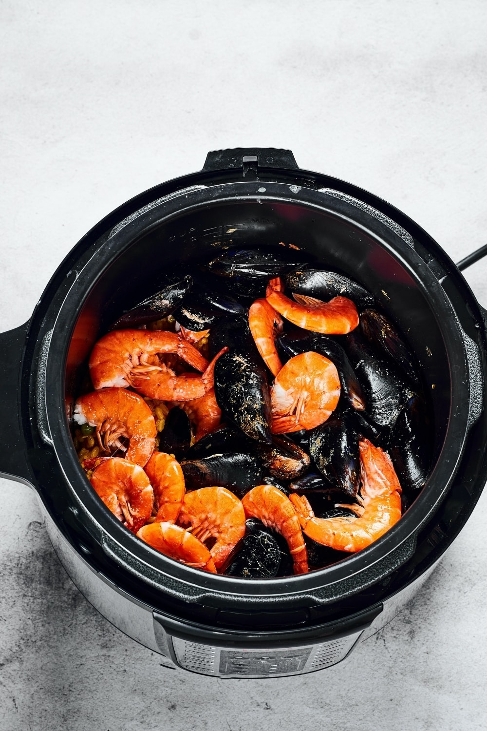 An instant pot with shrimp and mussels in it.