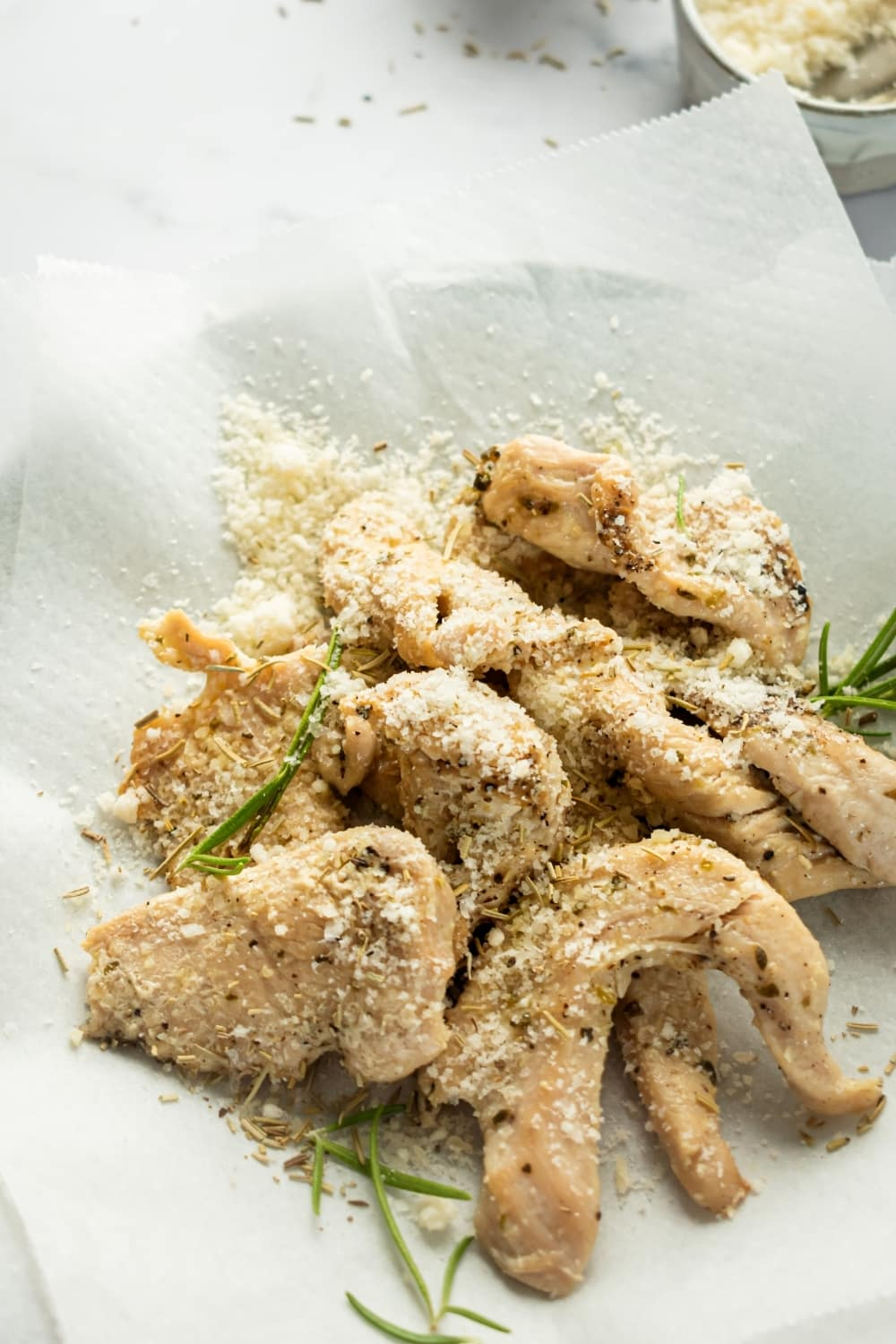 A bunch of chicken tenders and a piece of parchment paper. There is some Parmesan cheese on top of the chicken tenders.